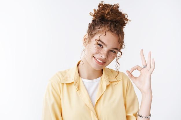 Портрет счастливая довольная очаровательная рыжая девушка кудрявая грязная булочка с веснушками на щеках, наклонив голову, сказать, хорошо, показать хорошо, жест одобрительно улыбаясь, согласен дать положительную рекомендацию, стоя на белом фоне