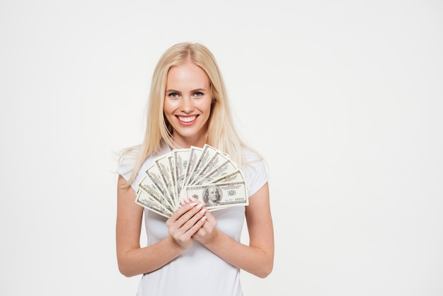 Portrait of a happy satisfied woman holding bunch of money