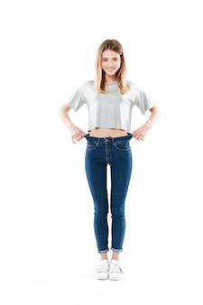 Ritratto di una giovane donna soddisfatta felice che sta e che mostra la sua perdita di peso isolata