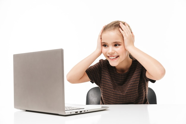 Portrait of happy school girl rejoicing and using silver laptop while sitting at desk in classisolated over white wall