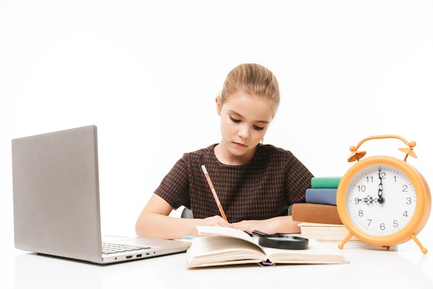 Portrait of happy school girl using silver laptop while studying and reading books in class isolated over white wall