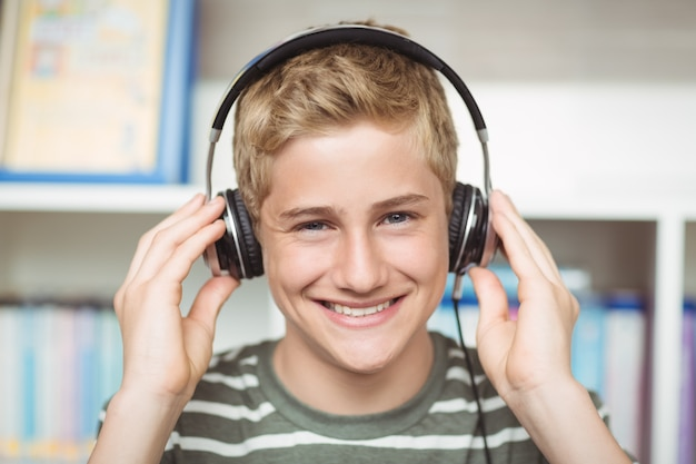 Portrait of happy schoolboy listening music on headphones in library