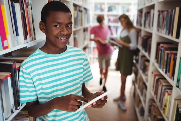 Portrait of happy schoolboy using digital tablet in library