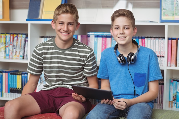 Portrait of happy schoolboys holding digital tablet in library