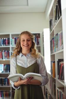 Portrait of happy schoolgirl holding book in library
