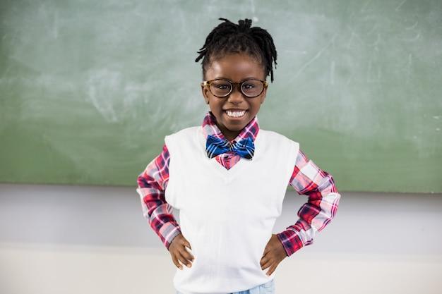 Portrait of happy schoolgirl standing with hand on hip