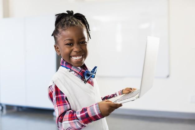 Portrait of happy schoolgirl using laptop in classroom