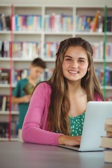 Portrait of happy schoolgirl using laptop in library