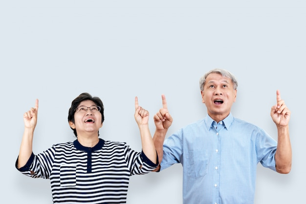 Portrait of happy senior asian couple gesture or pointing hand and finger up