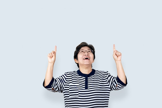 Portrait of happy senior asian woman gesture or pointing hand and finger up