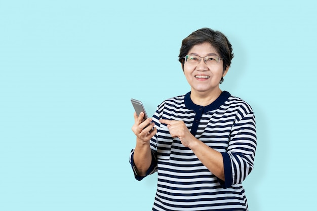 Portrait of happy senior asian woman holding or using smartphone and looking at camera on isolated background feeling positive enjoy and satisfaction. older female lifestyle concept  blue background.