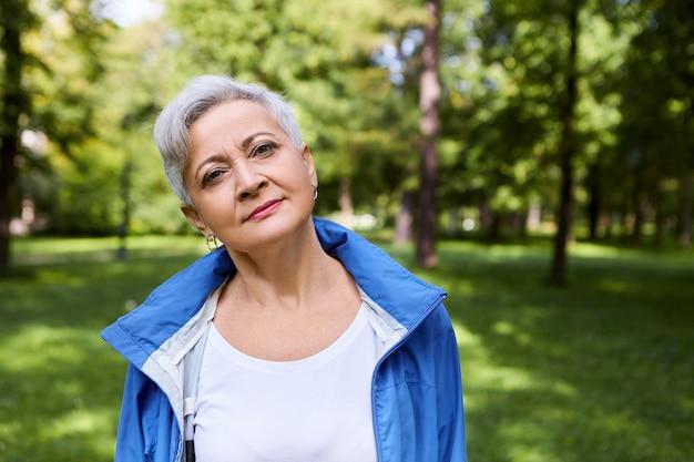 Ritratto di felice femmina caucasica senior con corti capelli grigi rilassante nel parco, con espressione facciale pacifica o premurosa, godersi il tempo da solo nella natura selvaggia, respirando aria fresca e fredda