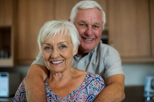 Portrait of happy senior couple embracing each other in kitchen at home