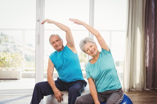 Portrait of happy senior couple exercising