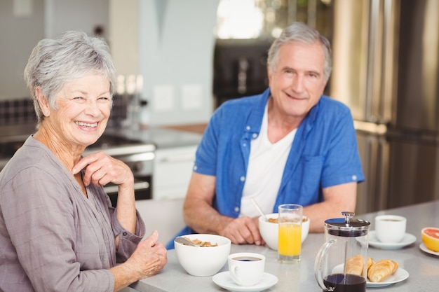 Portrait of happy senior couple having breakfast