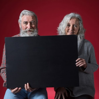 Portrait of happy senior couple holding black placard looking to camera against red background