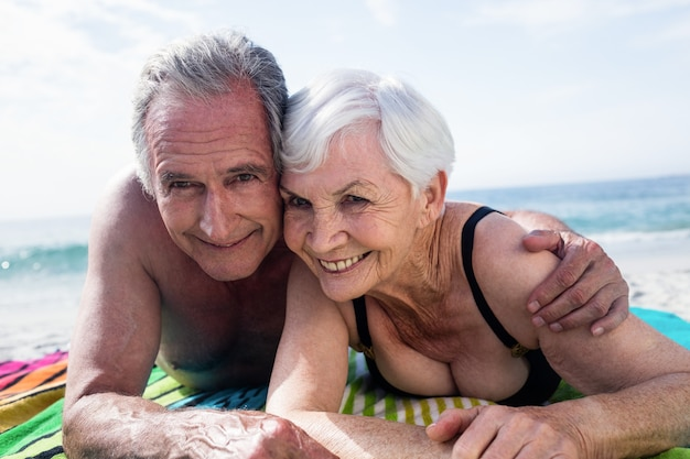 Portrait of happy senior couple lying on the beach