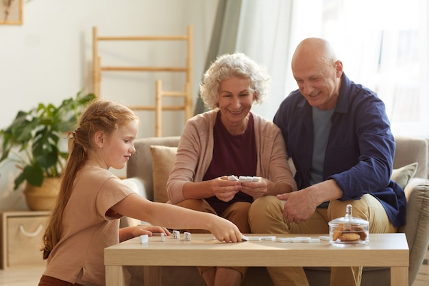 Portrait of happy senior couple playing board games with cute little granddaughter at home