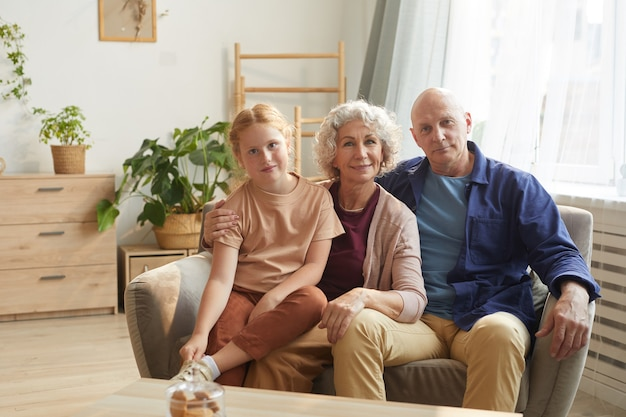 Portrait of happy senior couple posing with cute granddaughter while sitting on couch together in cozy home interior