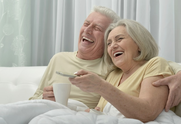 Portrait of a happy senior couple resting in bed