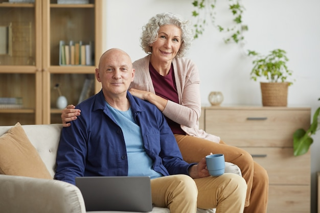 Portrait of happy senior couple smiling at camera while posing sitting on couch in cozy home interior