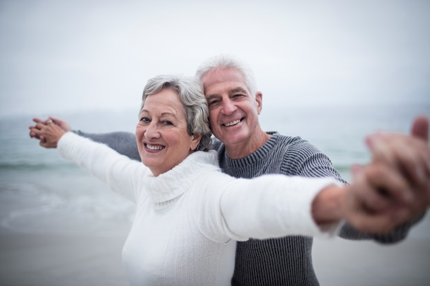 Portrait of happy senior couple standing with arms outstretched