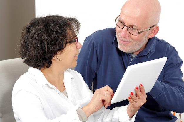Portrait of a happy senior couple using tablet digital
