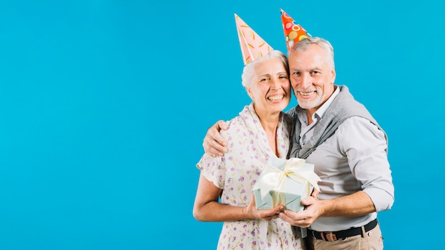 Portrait of happy senior couple with birthday gift on blue backdrop