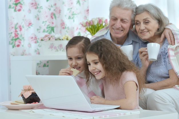 Portrait of a happy senior couple with grandchildren and laptop at home