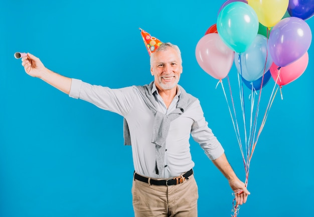 Portrait of a happy senior man holding balloons and party horn on blue backdrop
