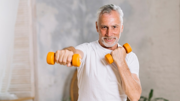 Portrait of happy senior man lifting weights
