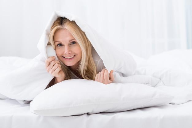 Portrait of happy senior woman in bed