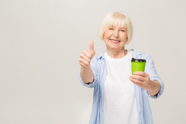 Portrait of happy senior woman drinking coffee isolated on white background. thumbs up.