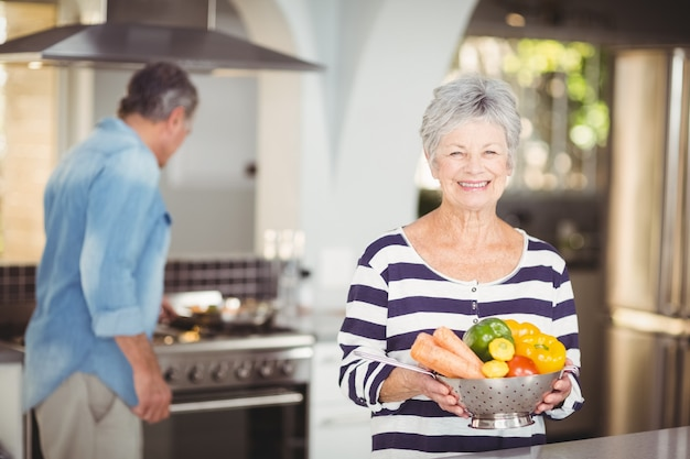 Portrait of happy senior woman holding colander with vegetables