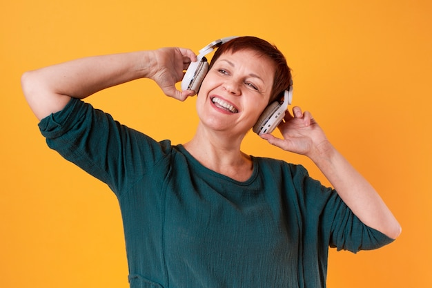 Portrait of happy senior woman listening to music