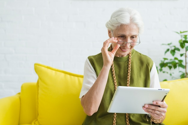 Portrait of happy senior woman looking in digital tablet