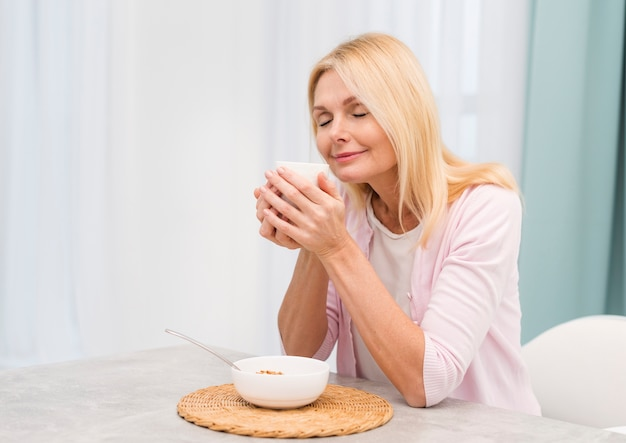 Portrait of happy senior woman serving breakfast
