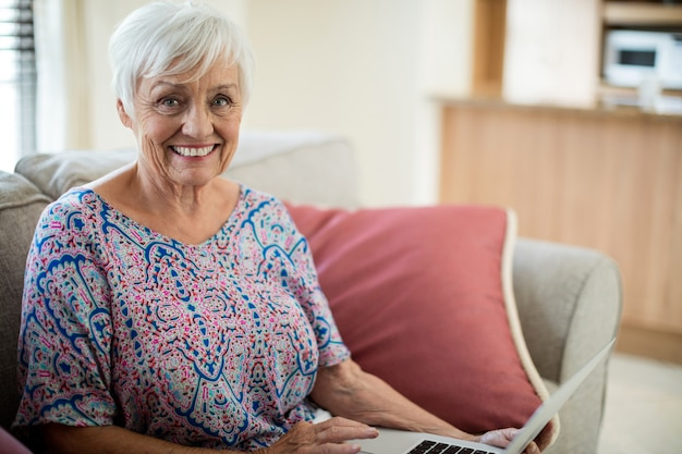 Portrait of happy senior woman using laptop in living room at home