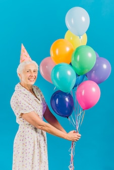 Portrait of a happy senior woman with colorful balloons on blue backdrop