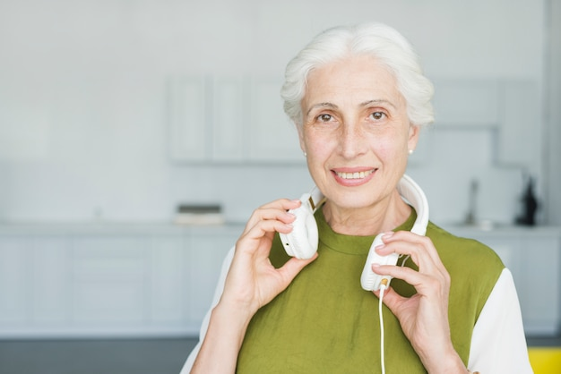 Portrait of happy senior woman with white headphone around her neck