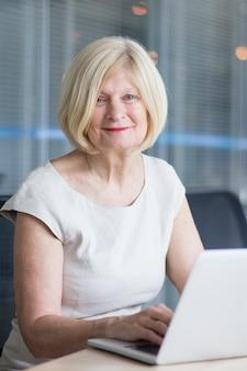 Ritratto di donna felice senior che lavora in ufficio
