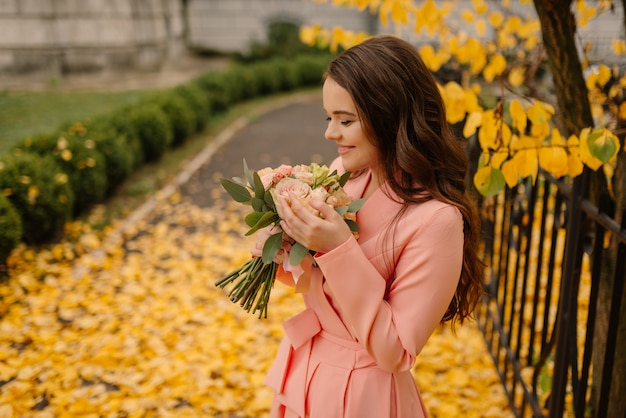 Portrait of happy sensual young brunette bride in rose wedding dress and standing in autumn park near vintage cathedral and holding wedding bouquet.