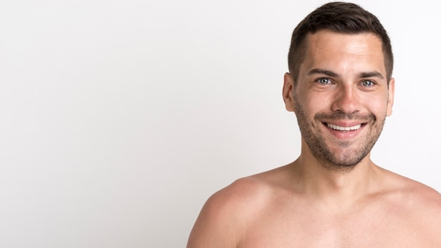 Portrait of happy shirtless man against white backdrop