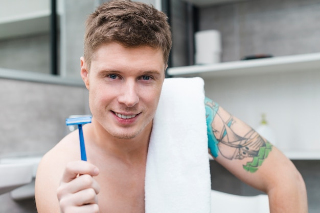 Portrait of a happy shirtless young man with towel over his shoulder holding blue razor in hand looking to camera
