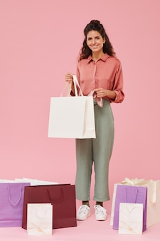 Portrait of happy shopaholic holding paper bag with purchase and smiling isolated on pink background