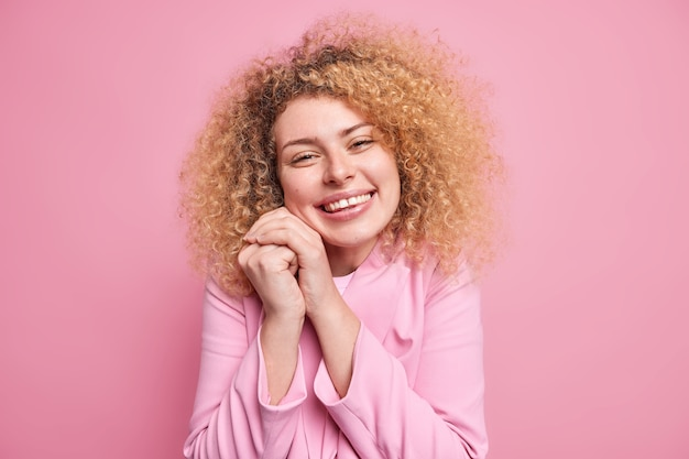 Portrait of happy sincere woman with curly hair keeps hands near face glad to hear heartwarming words or compliment smiles broadly dressed in pink jacket expresses positive emotions and feelings