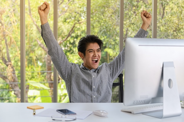 Portrait of happy smart young asian businessman looking to desktop computer and clench two fists and emotion glad in working room.
