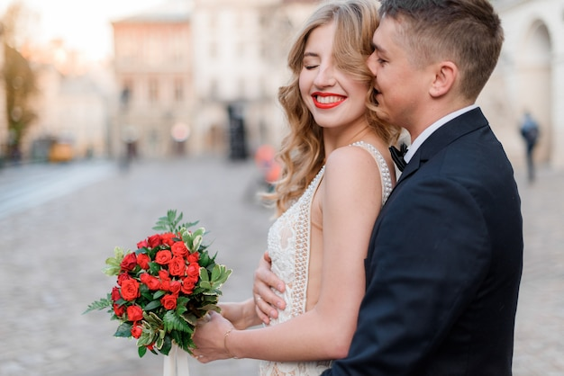 Portrait of happy smiled couple with bouquet made of red roses outdoors with closed eyes, romantic date