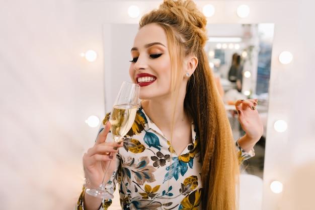 Giovane donna sorridente felice del ritratto con coiffure di lusso che beve vetro di champagne nel salone di parrucchiere