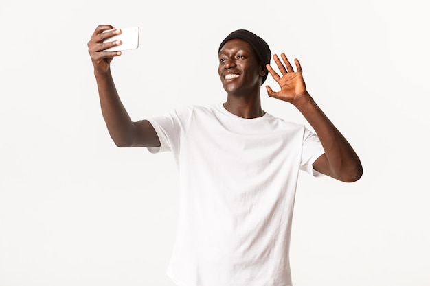 Portrait of happy smiling african-american guy talking with friends via video call, holding smartphone and waving hand in hello gesture